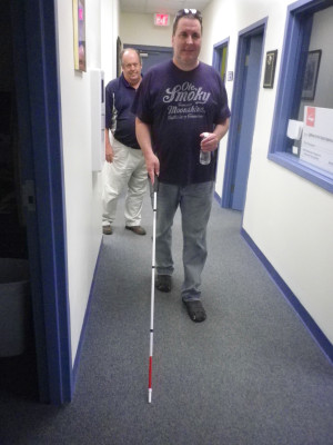 A male client with his white cane and his instructor